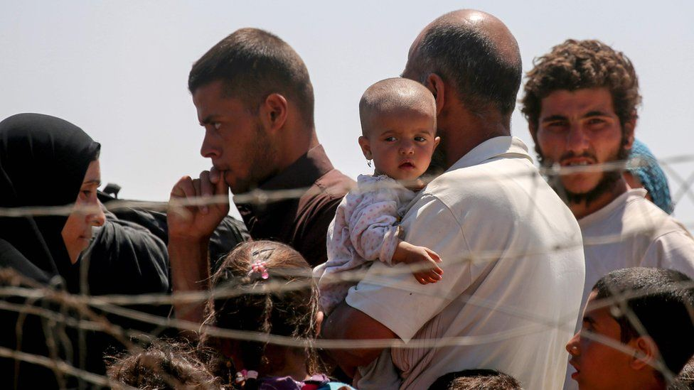 Displaced Syrians who have fled Raqqa stand at a temporary camp in the northern Syrian village of Ain Issa on 3 June 2017