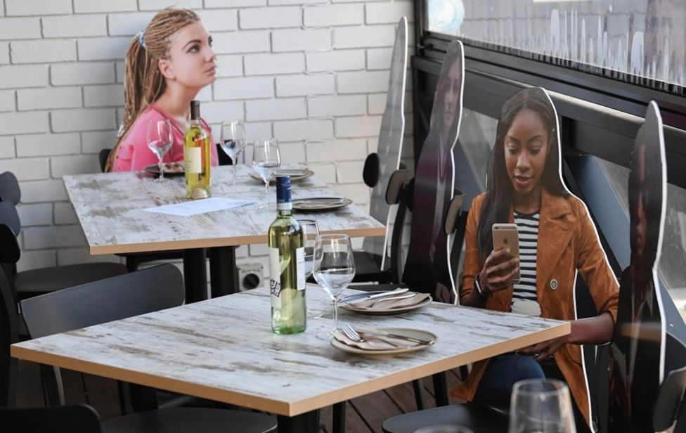 Cardboard cut outs of people are placed at dining tables in a restaurant