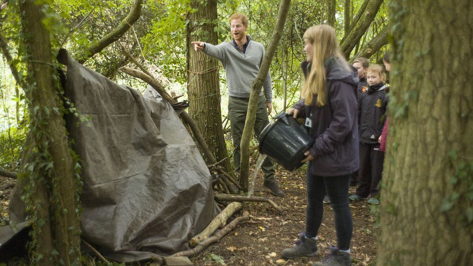 Prince Harry instructs youngsters to throw water over the shelter