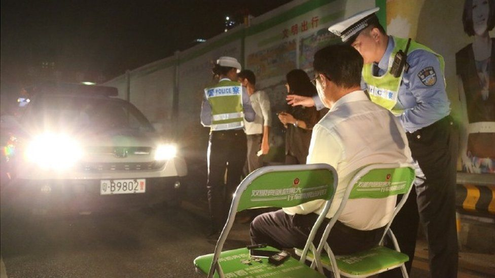 Shenzhen Traffic Police photo showing a man on a chair in the beam of car headlights with a police officer next to him