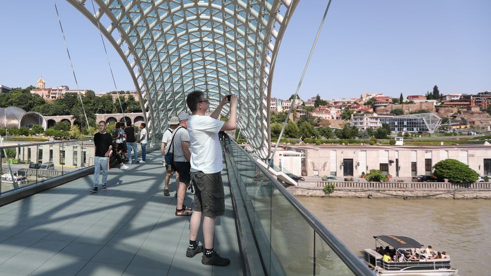 Tourists visit the Bridge of Peace at the old town of Tbilisi, Georgia 23 June 2019
