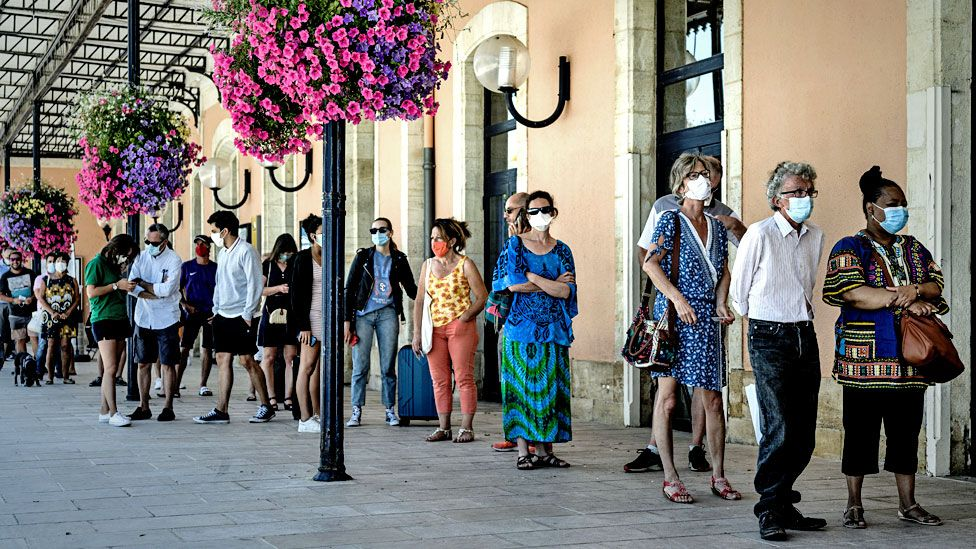 People queue to be screened outside the Arcachon railway station in France.