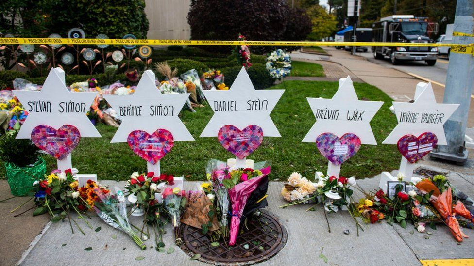 Flowers and stones are placed on the memorials erected outside of the Tree of Life Synagogue in Squirrel Hill