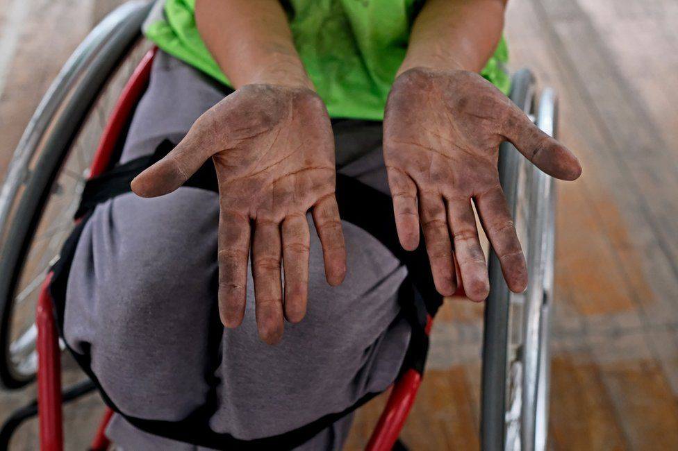 A player shows her hands, dirty from handling the ball
