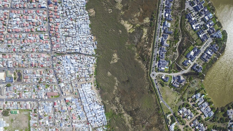 An aerial shot of Lake Michelle, a valuable and rich farm in Cape Town, South Africa, and a poorer community, Masiphumelele.
