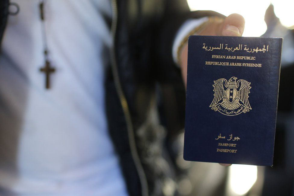 A man holds his Syrian passport
