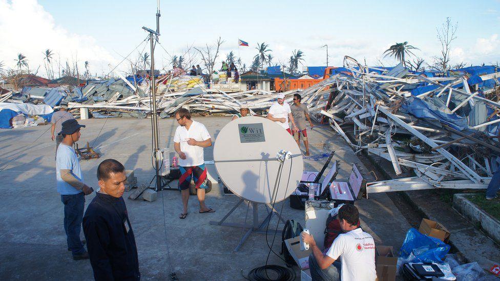 Setting network mast amid typhoon destruction