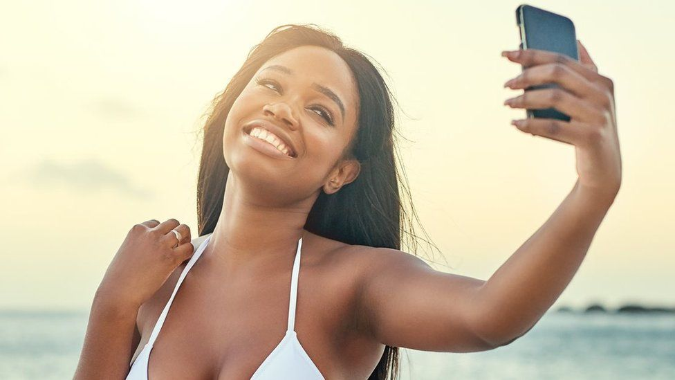 A woman takes a selfie on a beach