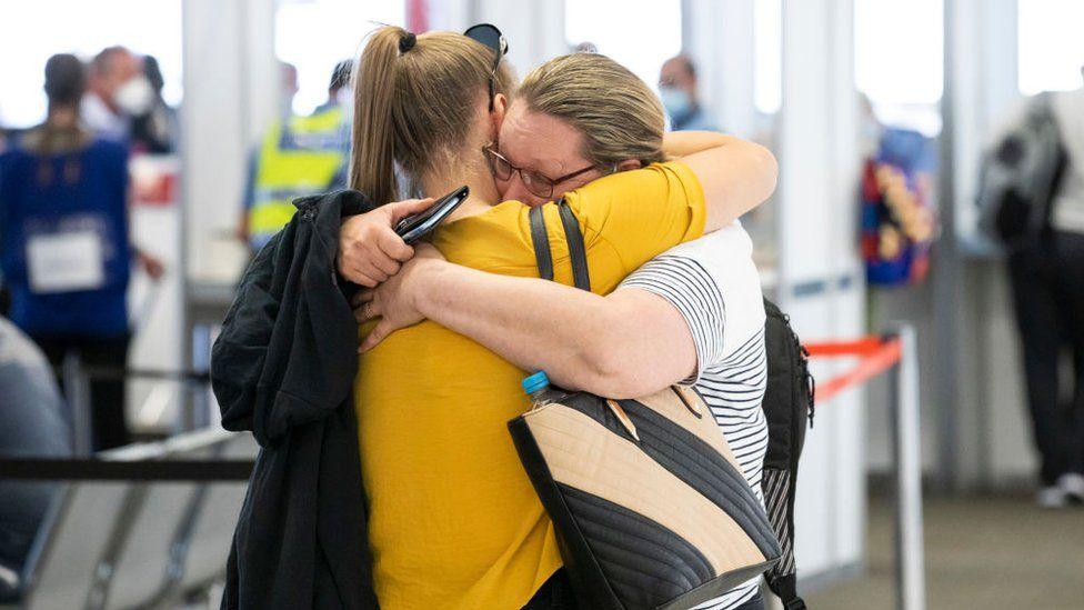 Двое членов семьи обнимаются после воссоединения в аэропорту Перта в декабре 2020 года после отмены закрытия государственной границы