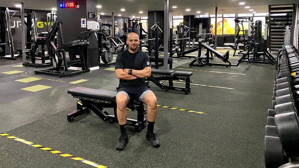Gym manager Rob Ward sitting in his gym with yellow tape marking floor areas.