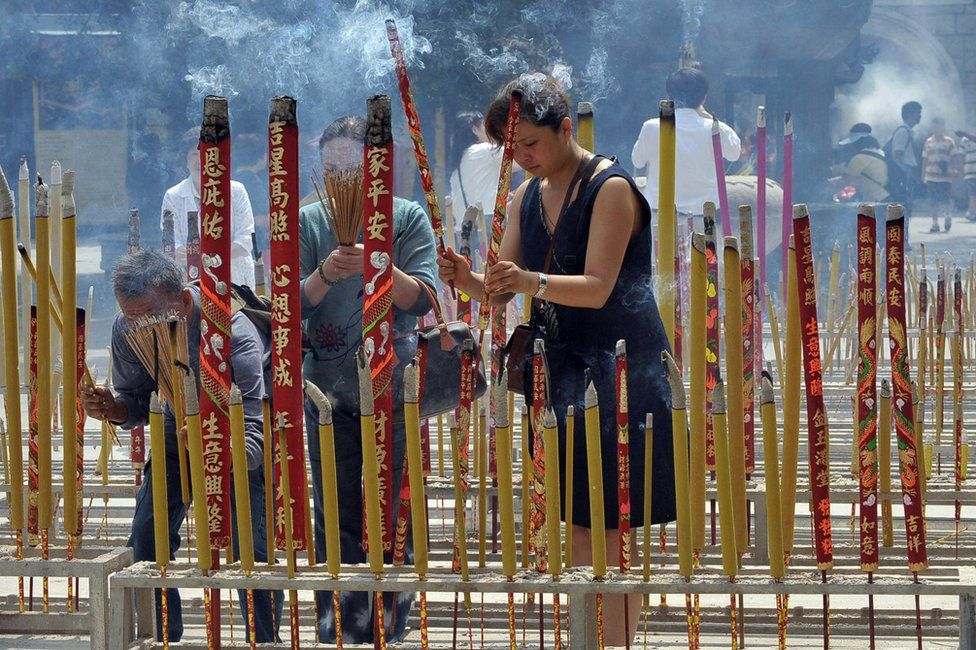 Visitors place incense sticks at the entrance of Po Lin monastery in Hong Kong on 12 May 2008