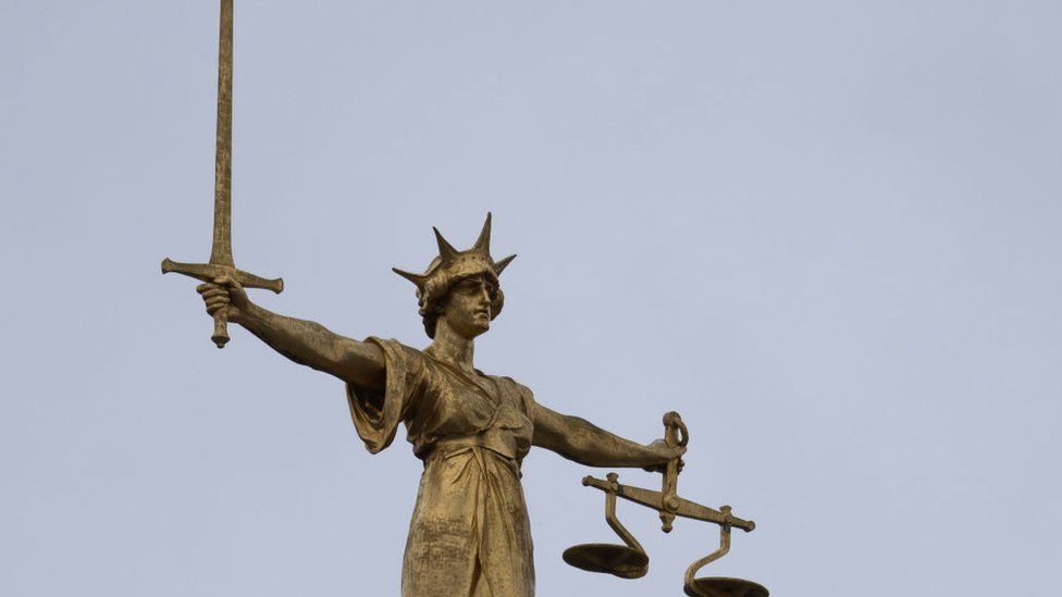 A statue of the Scales of Justice stands above the Old Bailey on January 19, 2021 in London, England