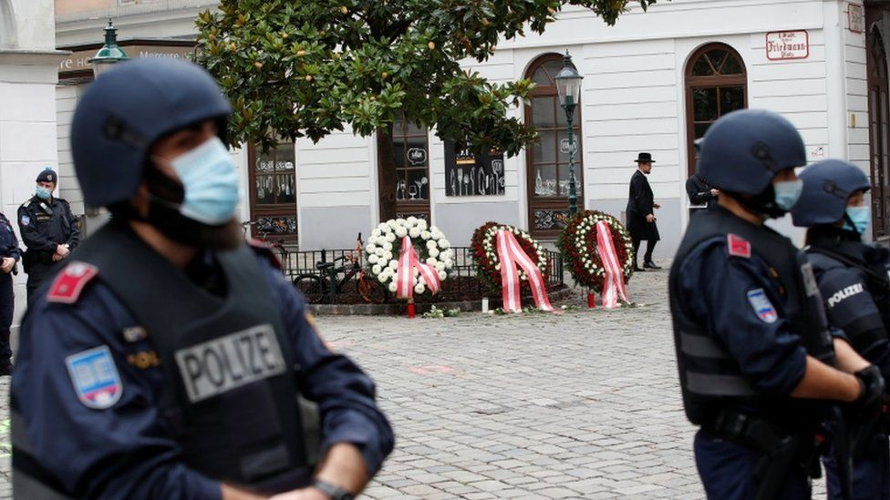 Police officers stand guard at the site of a wreath laying ceremony after a gun attack in Vienna,