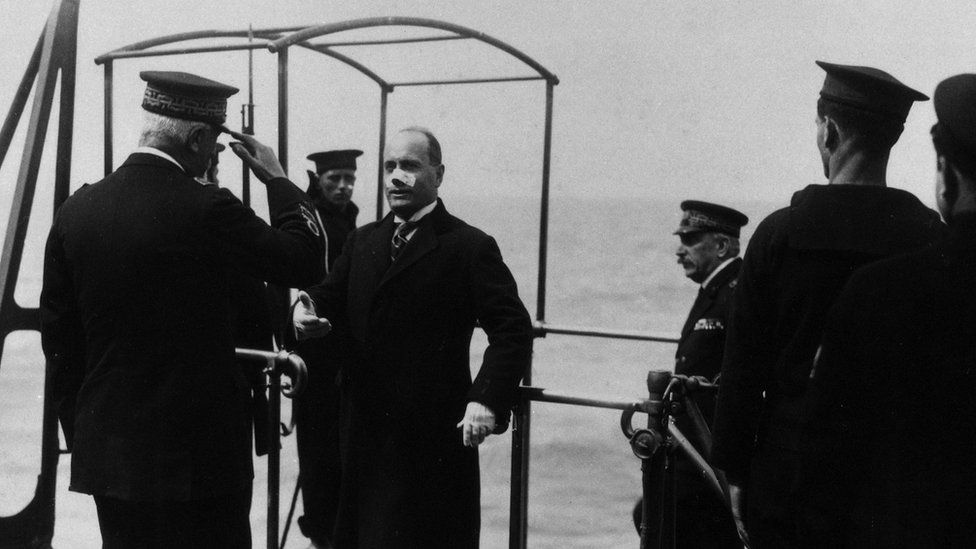 The head of the Fascist government Benito Mussolini welcomed by the admiral while boarding battleship Cavour with a bandaid over his nose.