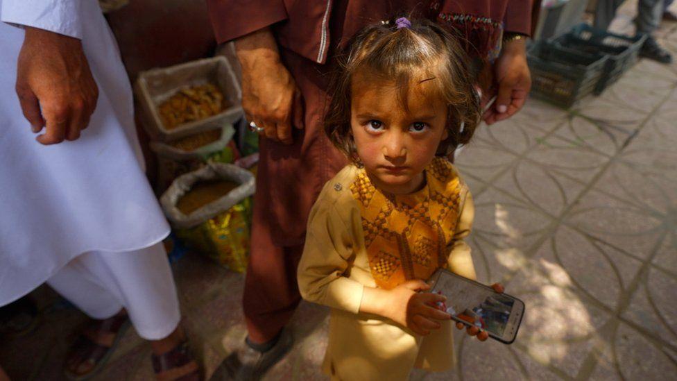 Chica con teléfono en el bazar de Balkh