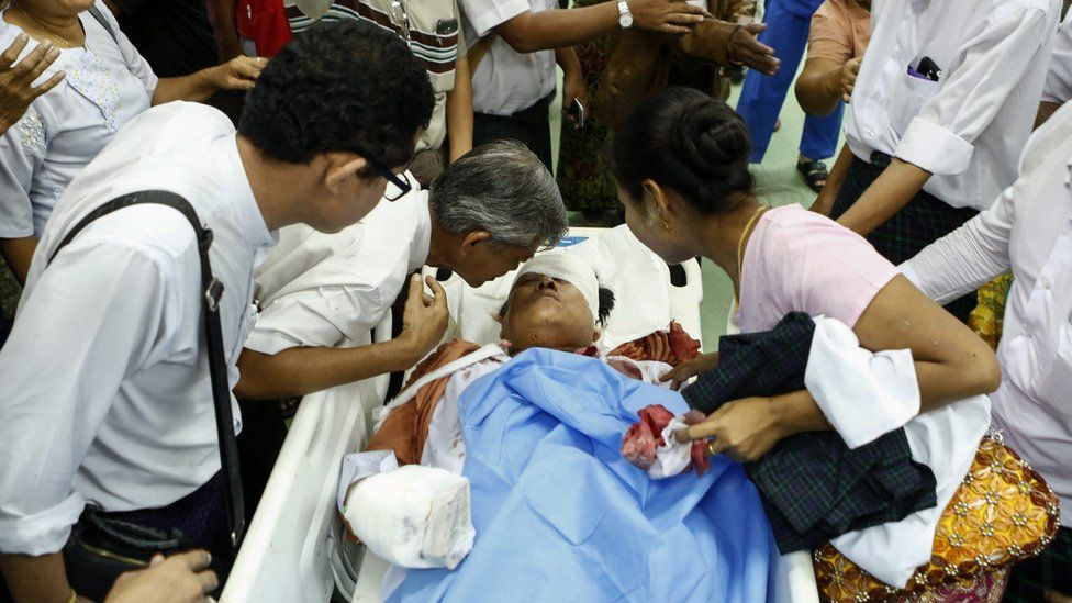 Injured Naing Ngan Lin lies on a bed as his father (L) and spouse (R) talks to him at Yangon General Hospital, Yangon, Myanmar (29 October 2015)