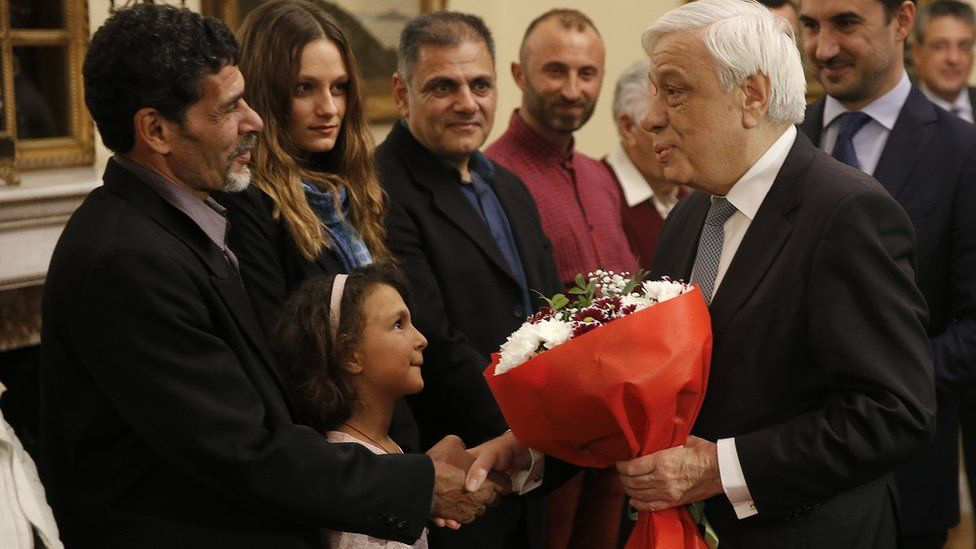 President Pavlopoulos (2nd R) congratulates migrant fishermen, 2 Jan 19
