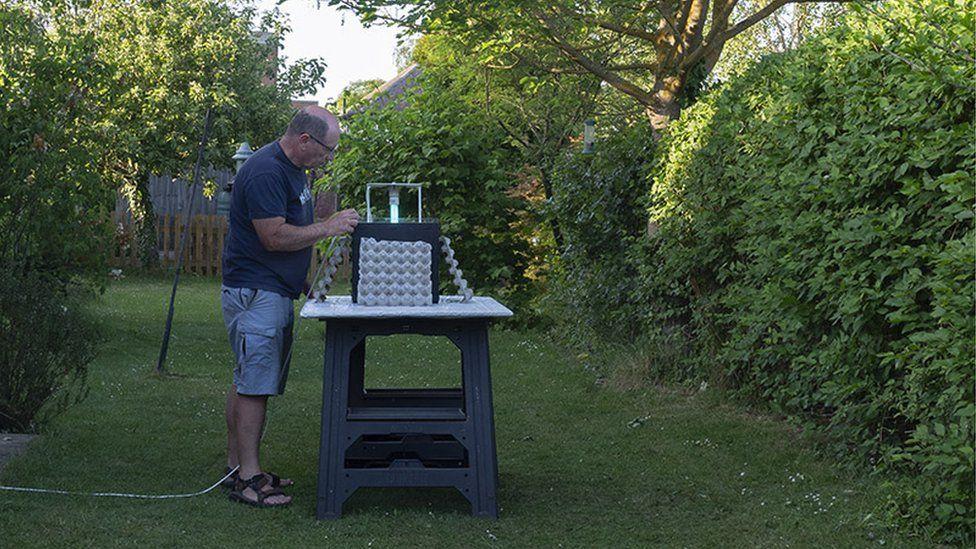 Paul Rule in garden setting up moth trap