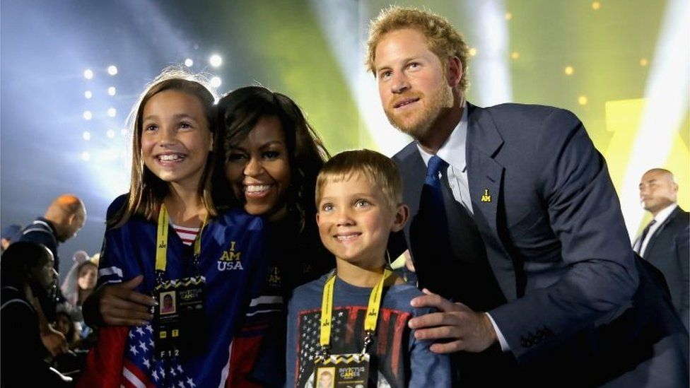 Michelle Obama and Prince Harry pose with children of servicemen and women competing in the Invictus Games