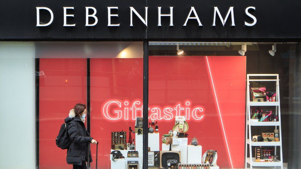 A woman walking past Debenhams