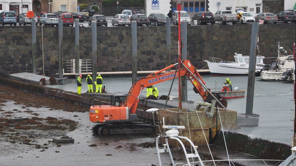 Repairs being carried out to piling and pontoon wall
