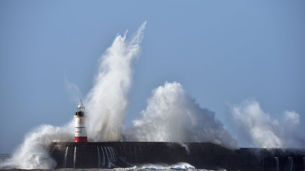 Waves crash into lighthouse in Newhaven