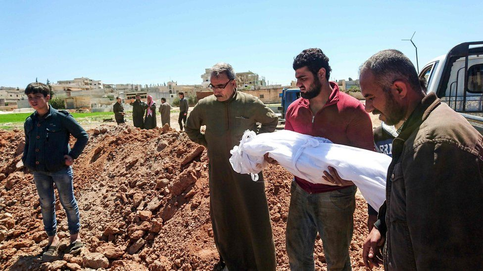 Syrians bury the bodies of victims of a a suspected chemical attack in Khan Sheikhoun (5 April 2017)