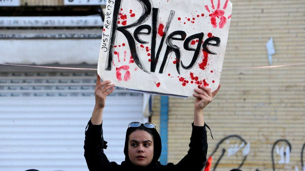 An Iranian mourner holds a placard during the final stage of funeral processions for the general Qasem Soleimani