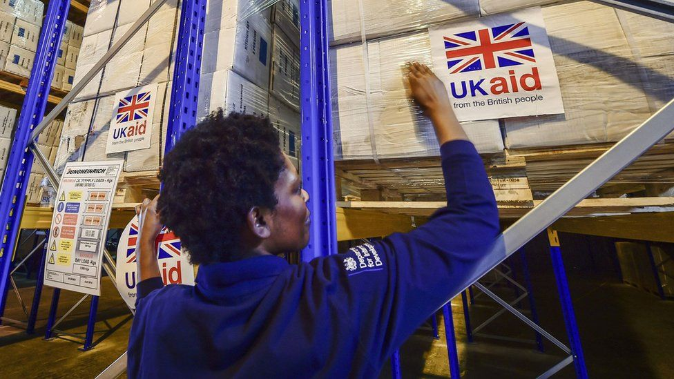 File photo dated August 2014 of logistics officer placing UK Aid stickers onto cargo pallets containing British aid items destined for areas suffering humanitarian crisis