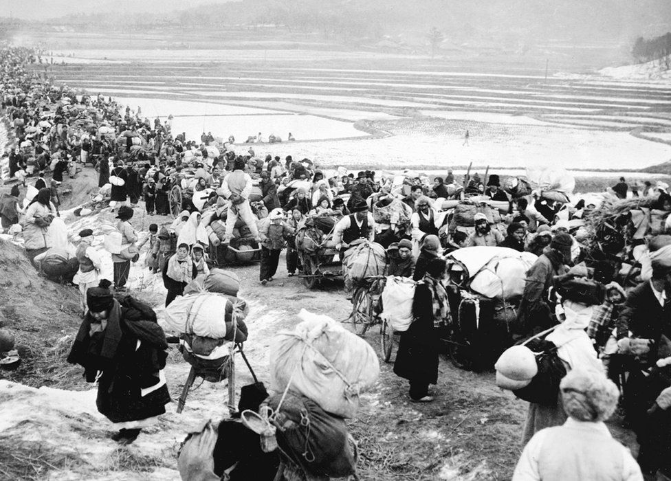 Unlocated picture taken 18 January 1951, shows Korean refugees fleeing to the south, as they are passing by frozen rice fields.