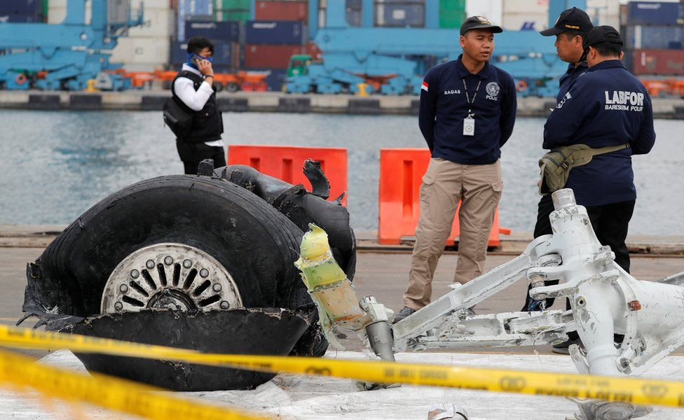 Indonesian forensic officers stand beside the damaged landing gear of Lion Air flight JT610 in Jakarta, 5 November 2018