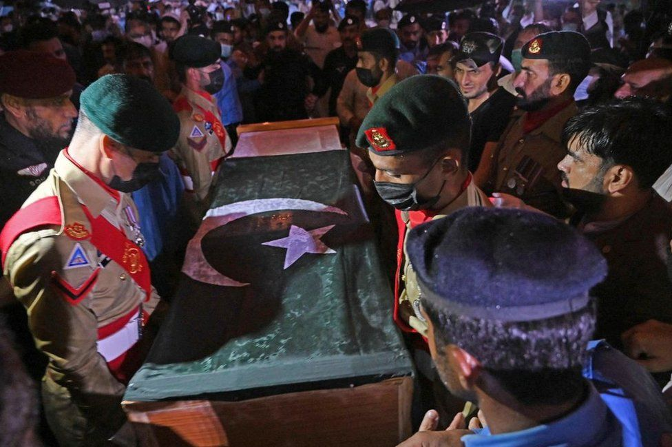 Soldiers prepare to place the flag-draped coffin of nuclear scientist Abdul Qadeer Khan during his funeral