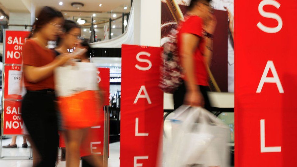 Shoppers walk past sales signs in a department store in Sydney