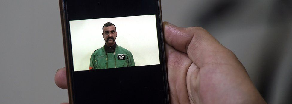 A Pakistani man watches the latest video statement released by Pakistan's military authorities of the Indian Wing Commander pilot Abhinandan Varthaman on his smartphone