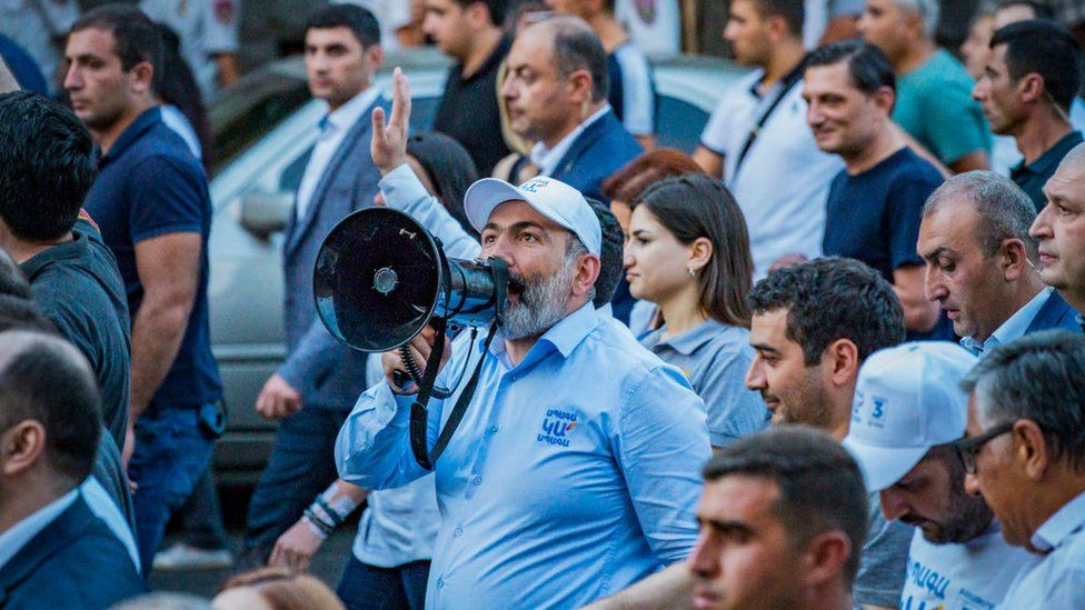 Nikol Pashinyan talks with a loudhailer to his supporters in a march through the streets of Yerevan