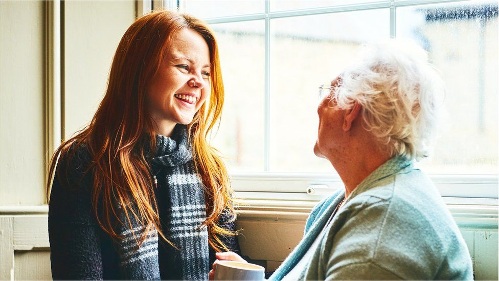 A granddaughter and her grandmother smile together beside a window
