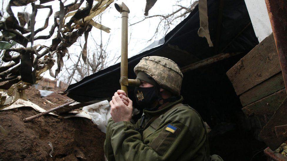 Украинский солдат, глядя в телескоп, стоял в окопе