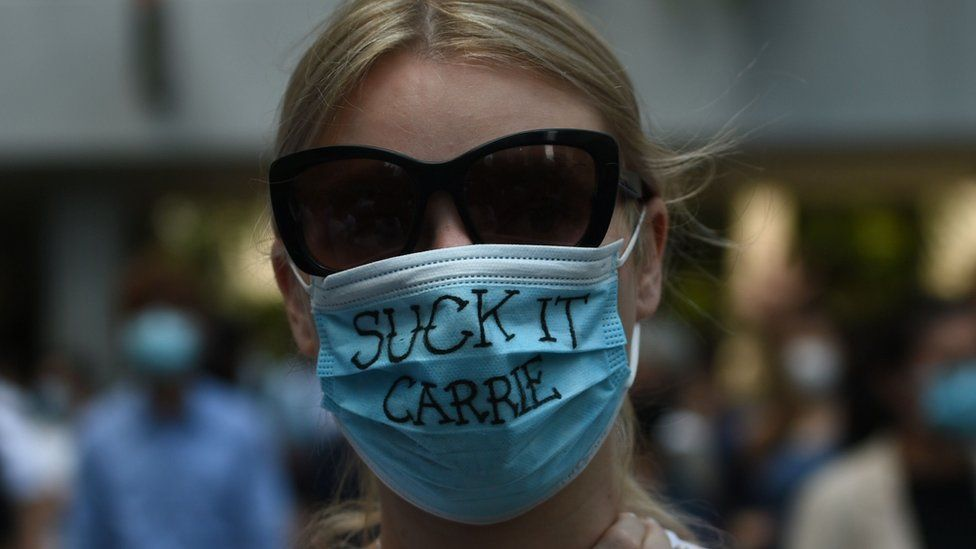 """A pro-democracy demonstrator wears a mask that reads """"suck it Carrie"""" as she and others gather at Chater Garden"""