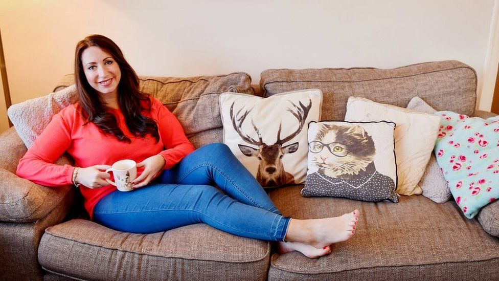 Paula Williamson sitting on the sofa at home