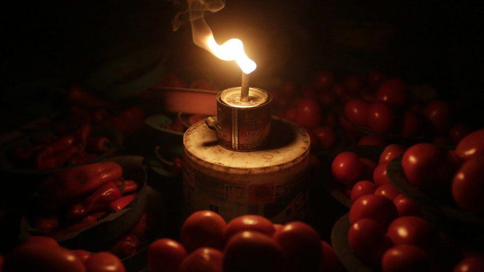 A vegetable seller in Lagos uses an artisanal lantern - Monday 20 February 2017