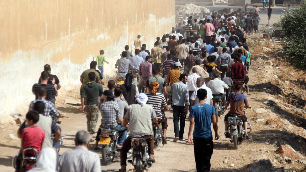 Syrians walk and ride motorcycles during the funeral of seven members of the Syrian civil defence volunteers, also known as the White Helmets, during their funeral in Sarmeen