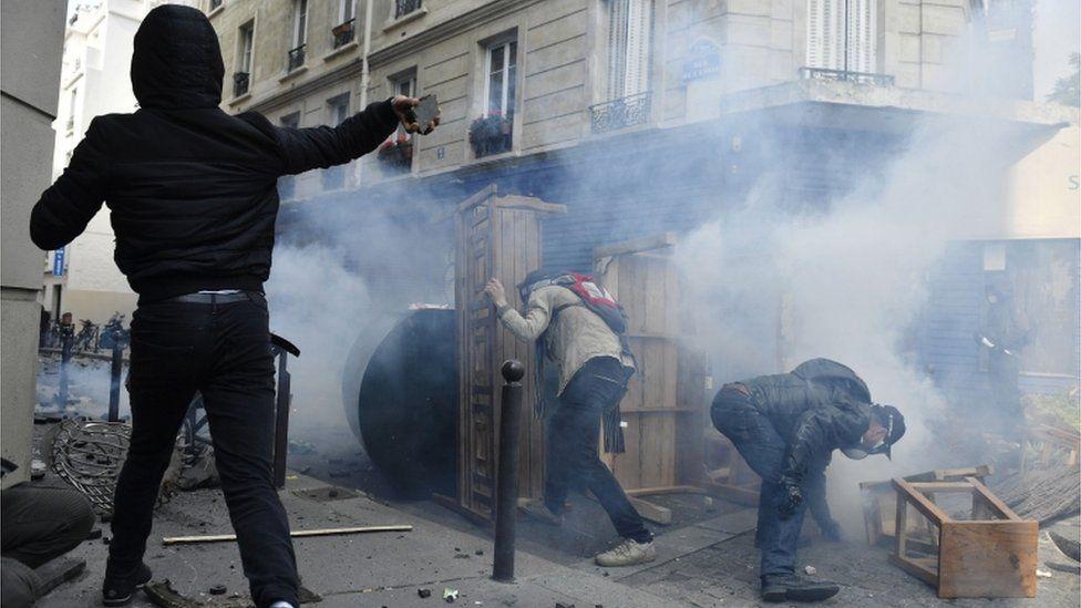 Demonstrators in Paris hide behind barricades and throw paving stones