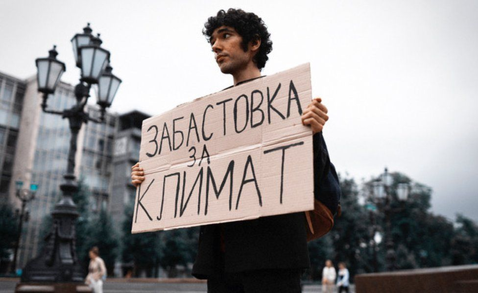"""Protester Arshak holds a sign reading """"climate strike"""" in Moscow"""