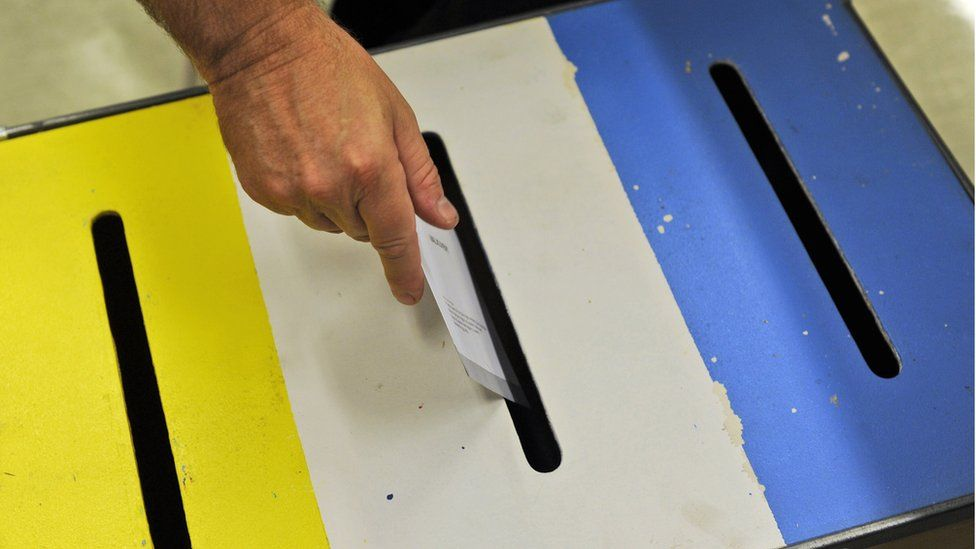 A voter puts their paper into a ballot box