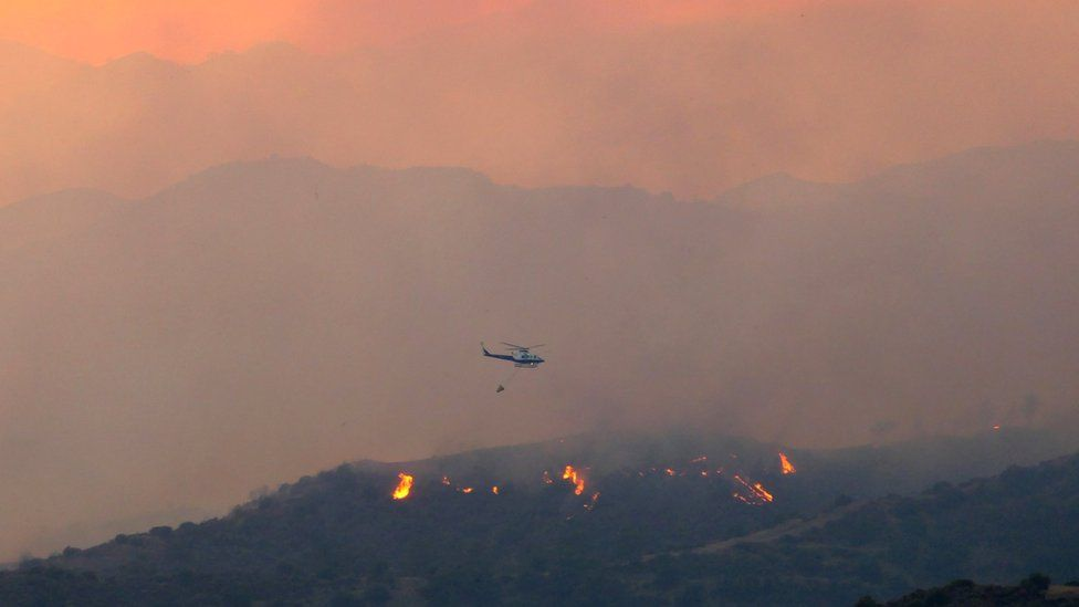 A helicopter flies over a forest fire, in the Larnaca mountain region, Cyprus, 3 July 2021