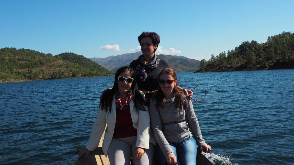 Three teachers on a boat going to visit Niko