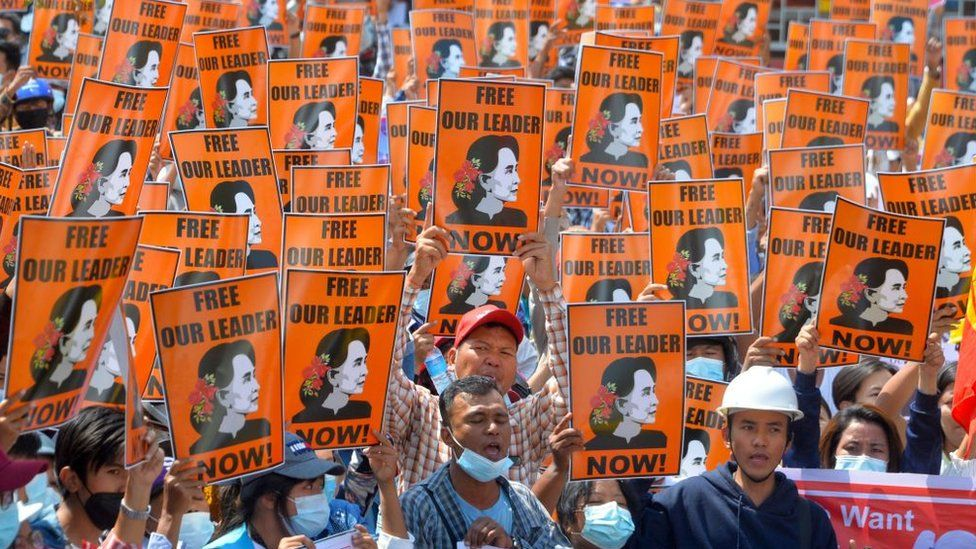 Protesters hold posters with the image of detained civilian leader Aung San Suu Kyi during a demonstration against the military coup in Naypyidaw