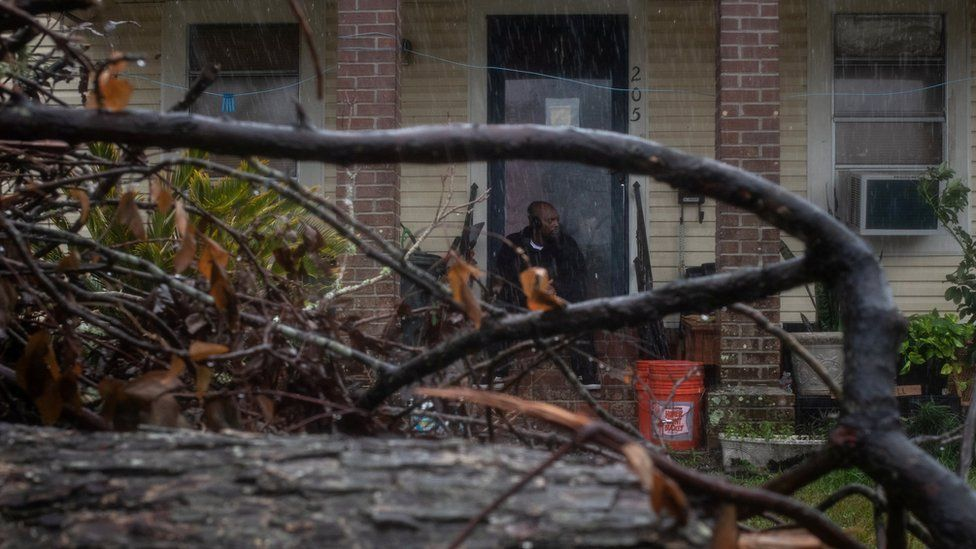 A man waits for the arrival of Hurricane Delta, surrounded by debris that was blown into his garden by Hurricane Laura