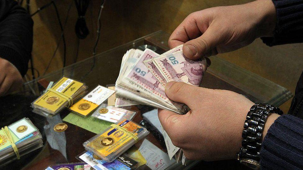Man counts Iranian banknotes