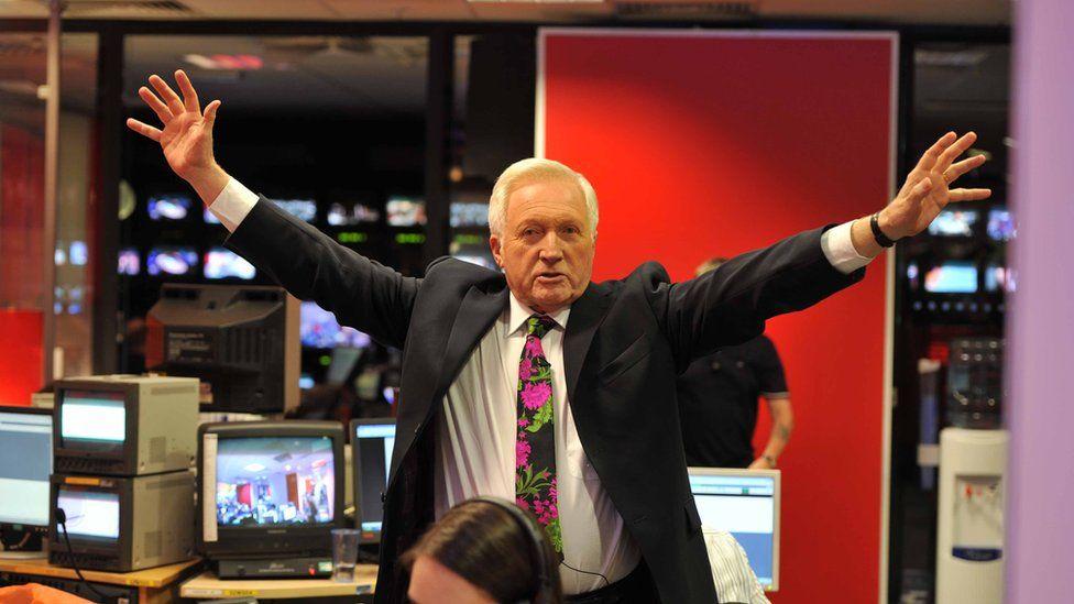 David Dimbleby holding his arms up
